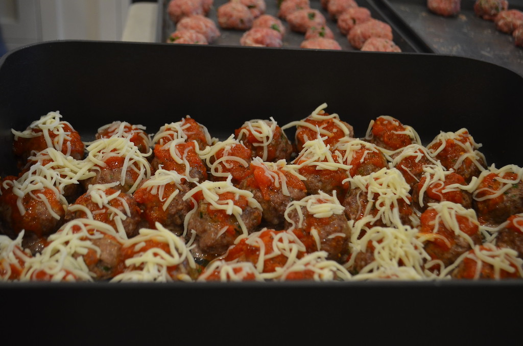 meatballs in large pan with cheese and sauce on top
