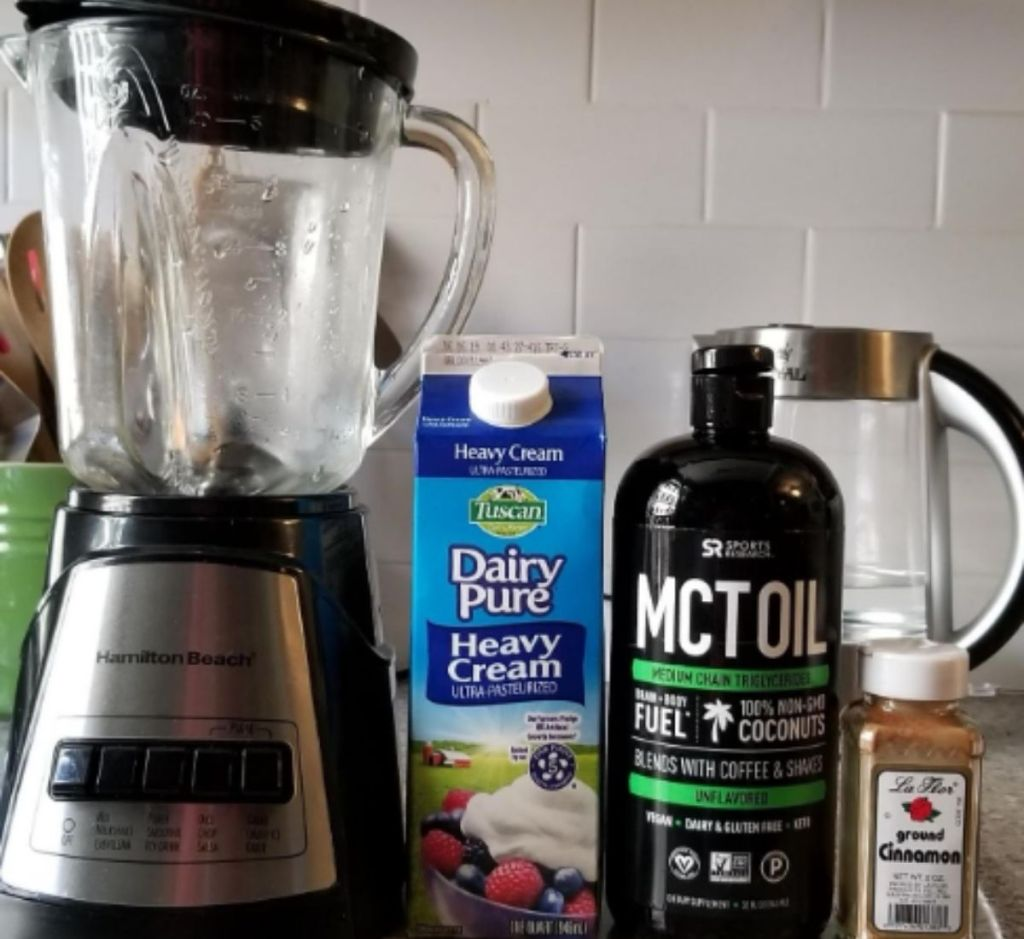 A blender on a counter next to MCT oil and heavy cream