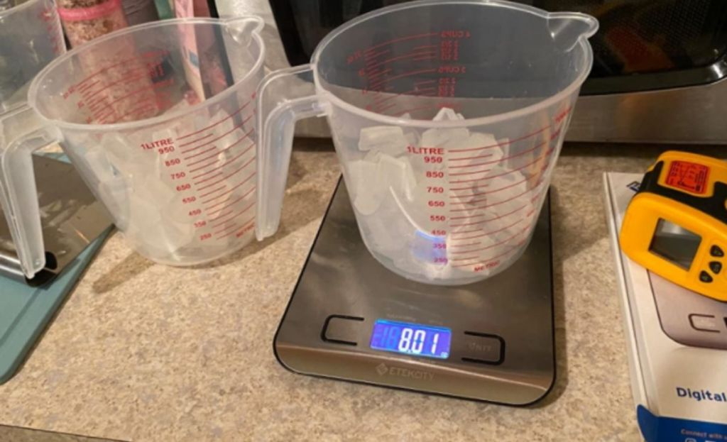 A digital food scale on a counter with a measuring cup full of ice on it