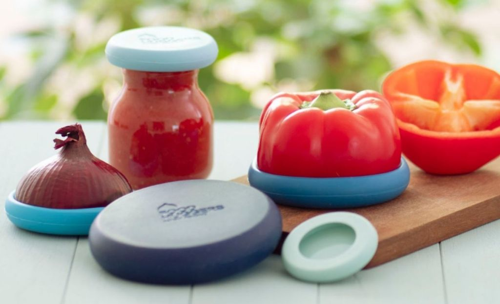 A red pepper and an onion with food huggers covering them on a table