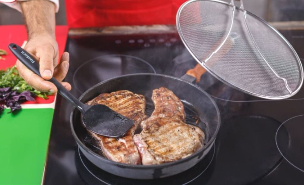 Someone cooking chicken in a pan and holding a grease splatter screen