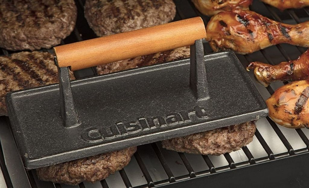 A grill press being used on patties on a grill