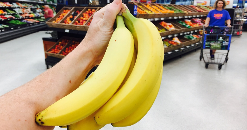 hand holding up bananas at grocery store