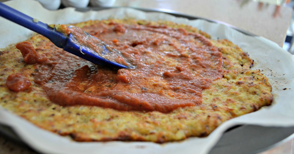 keto cauliflower crust recipe spooning on the sauce