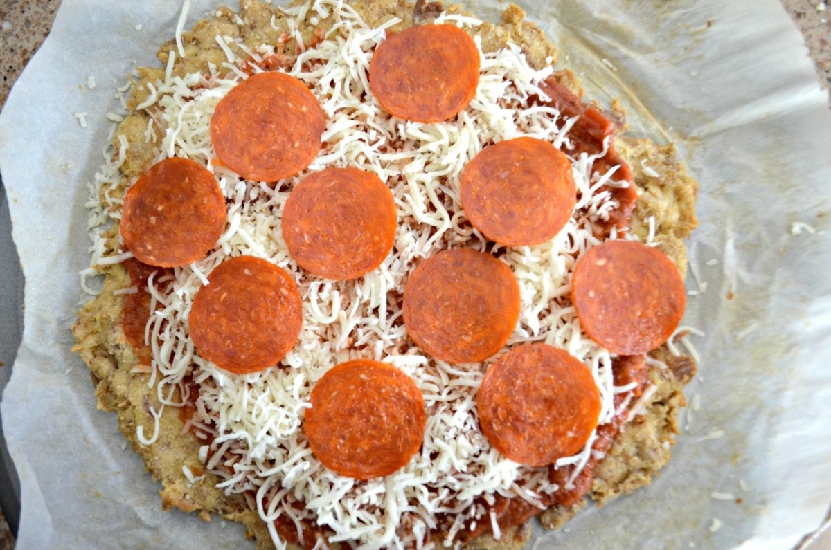 Keto chicken pizza crust topped with cheese and pepperoni.