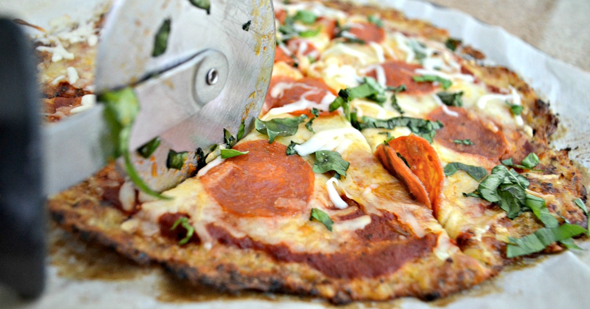 keto cauliflower pizza recipe being cut with a pizza cutter