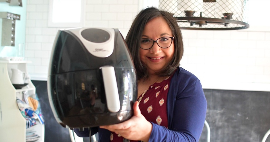 woman holding an air fryer in the kitchen