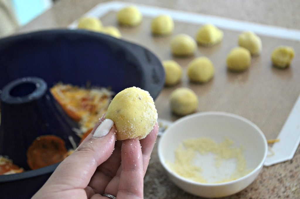 holding keto dough ball rolled in parmesan cheese