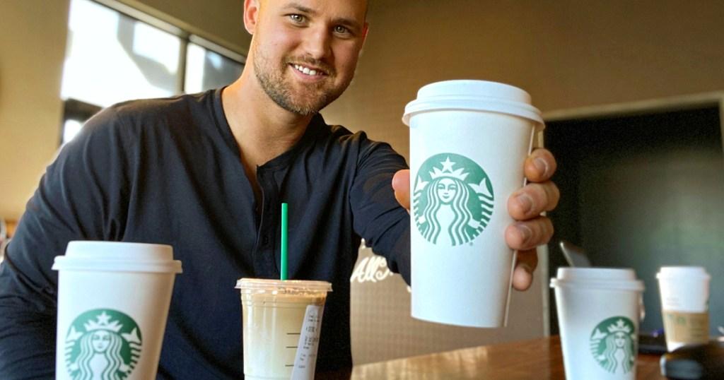 man holding up Starbucks drinks