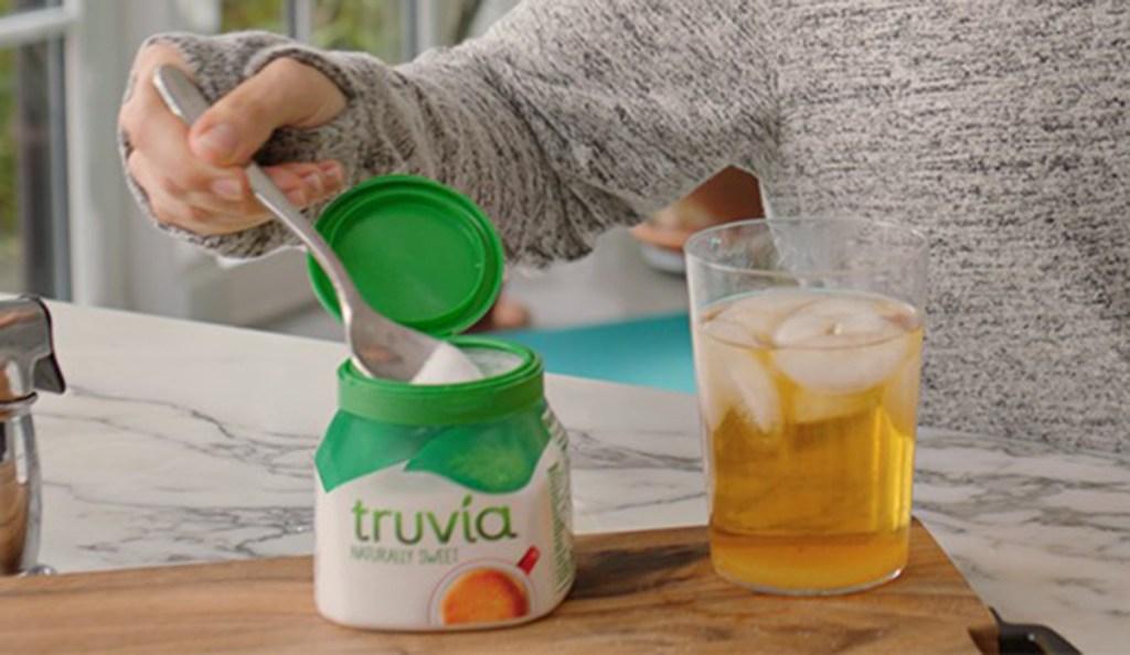 person putting truvia in tea