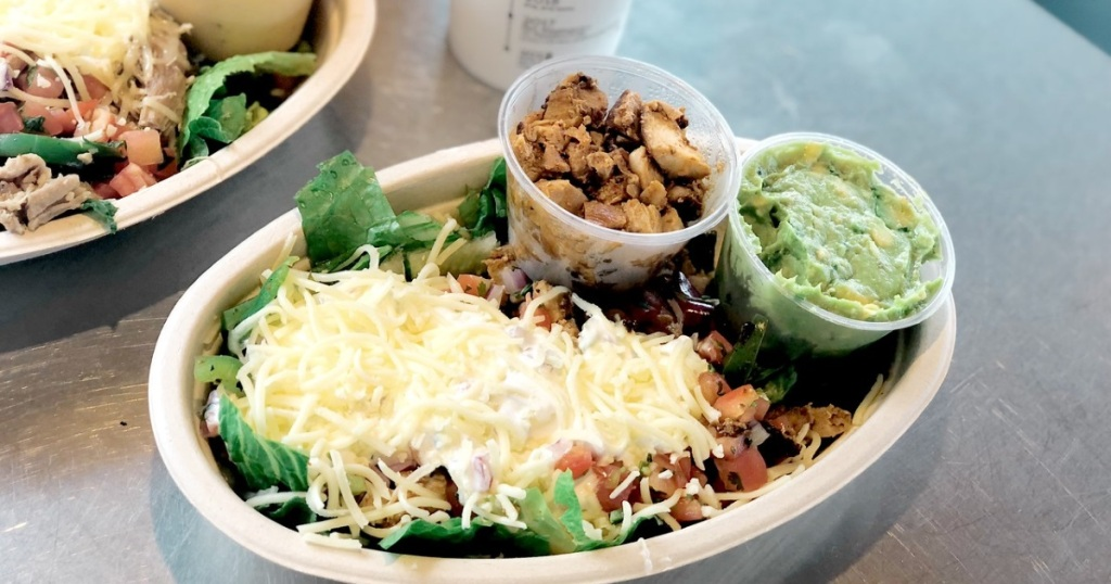 Chipotle bowl with shredded cheese, chicken, and guac