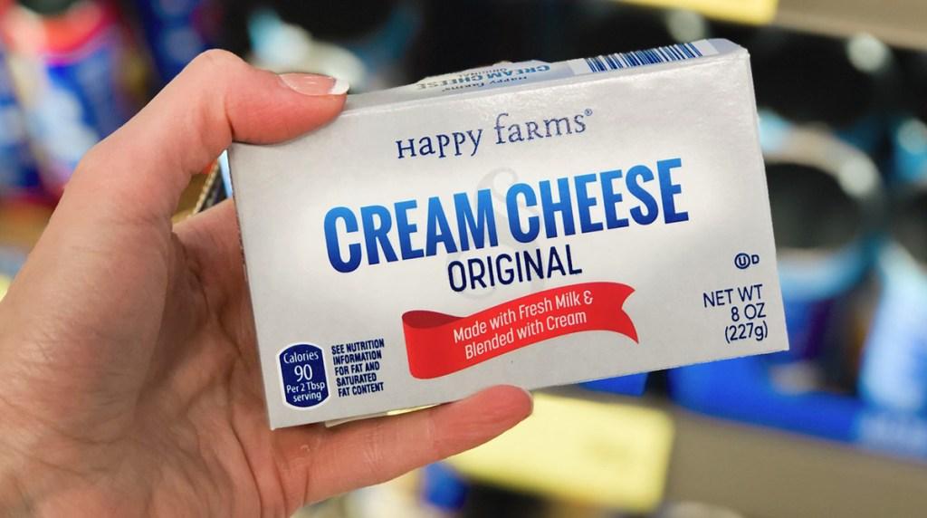hand holding block of cream cheese