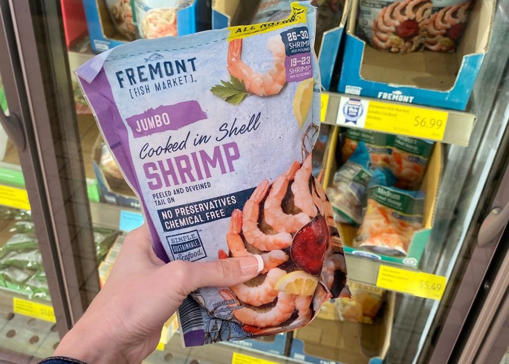hand holding a bag of shrimp at aldi