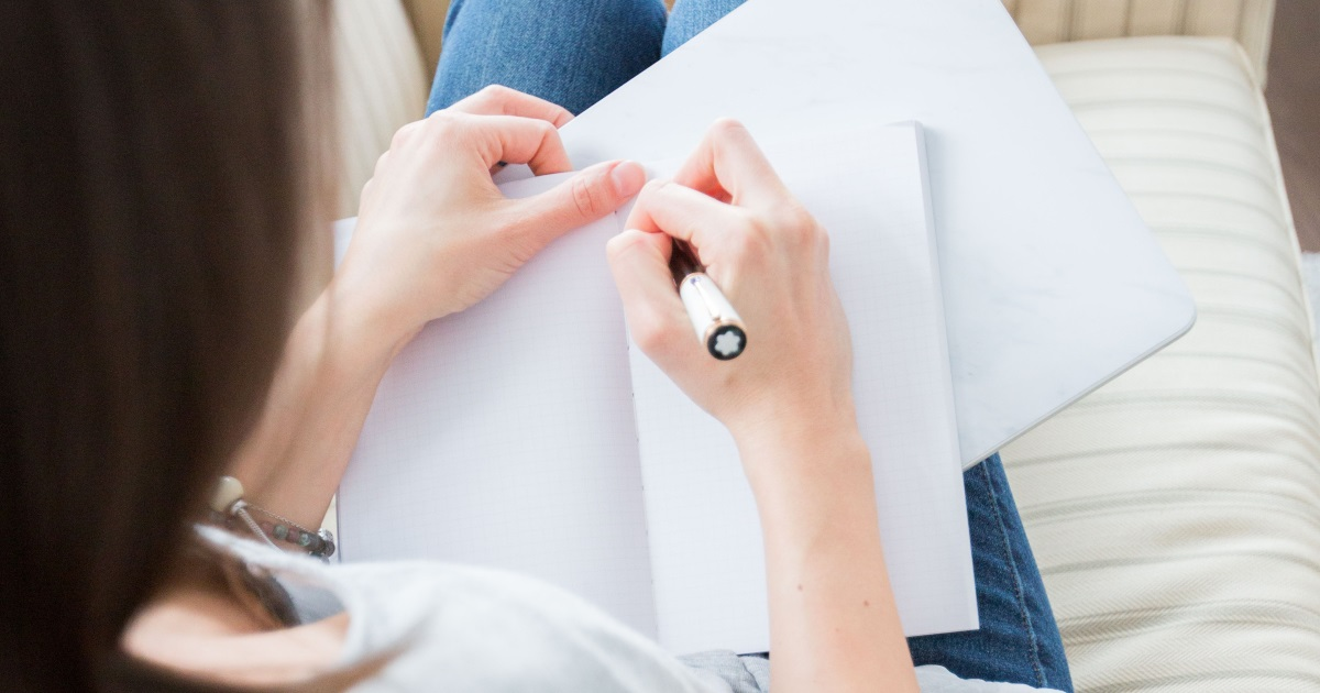a woman writing in a journal as a way of how to stop emotional eating