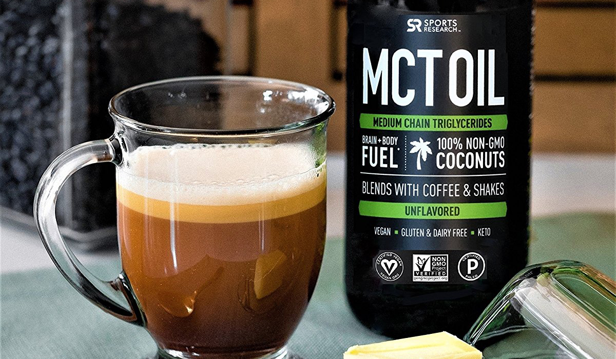 keto mct oil supplements – bottle of MCT oil next to a cup of coffee