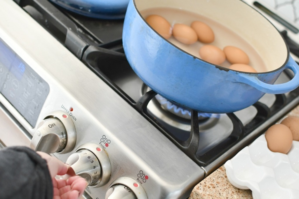 turning on a stove to cook eggs