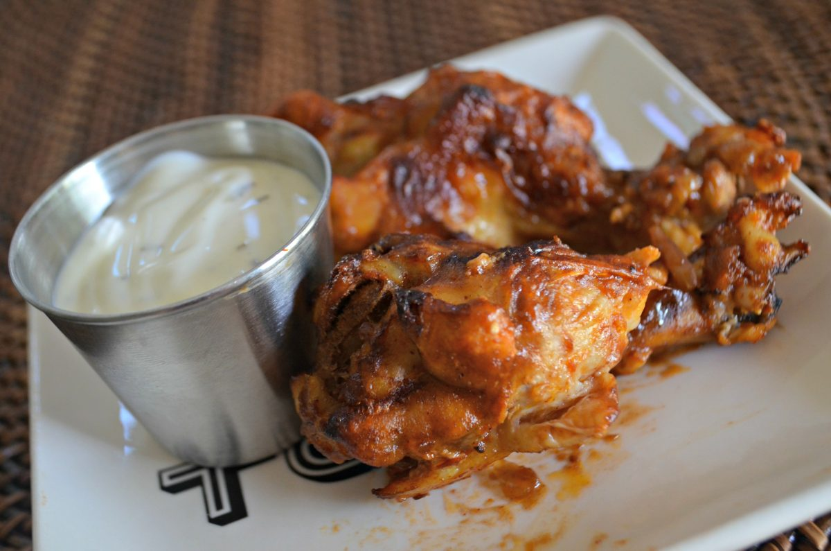 Keto Slow Cooker Buffalo BBQ Wings - on a plate with dipping sauce