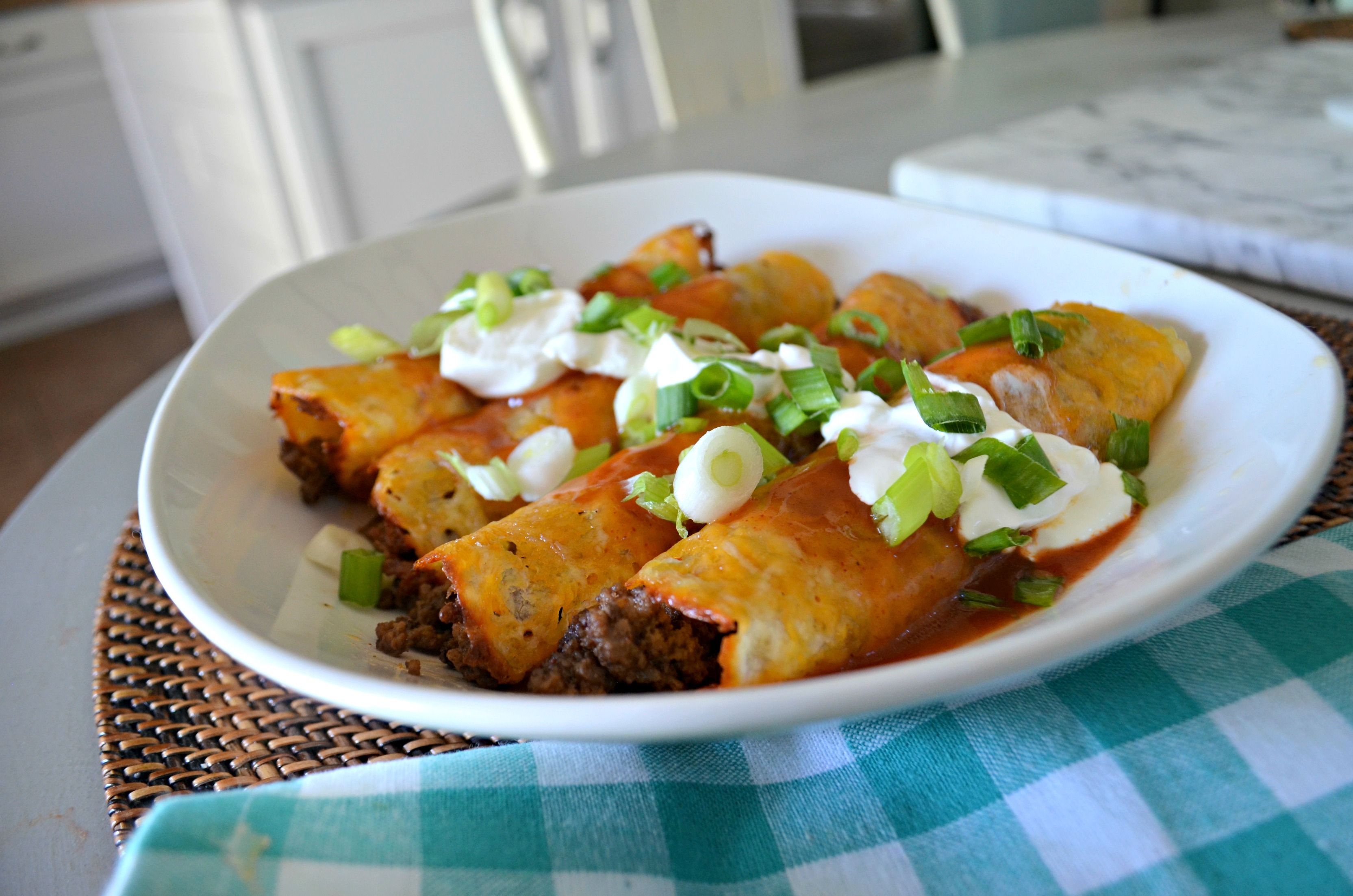 The ground beef keto enchiladas are arranged on a platter with sour cream and chopped green onion