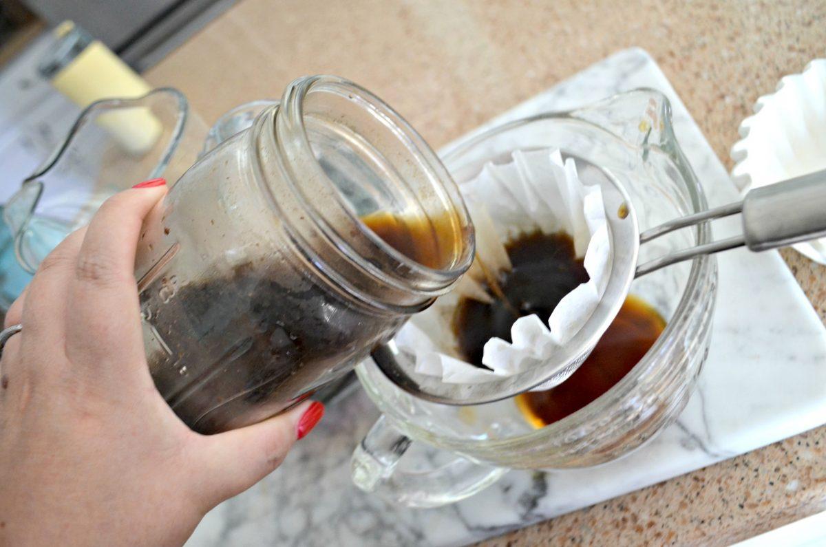 delicious keto cold brew coffee – pouring through a strainer