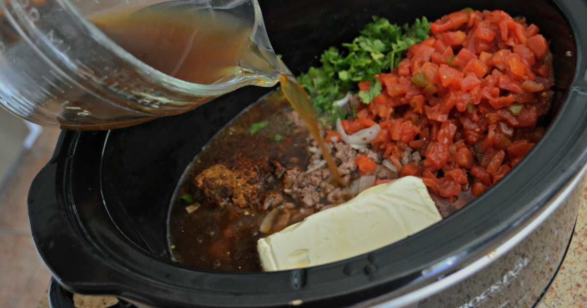 slow cooker keto taco soup - pouring liquids into the slow cooker