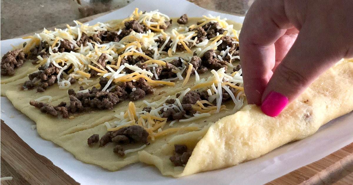 Easy Keto Taco Stuffed Breadsticks – folding up the dough around the meat
