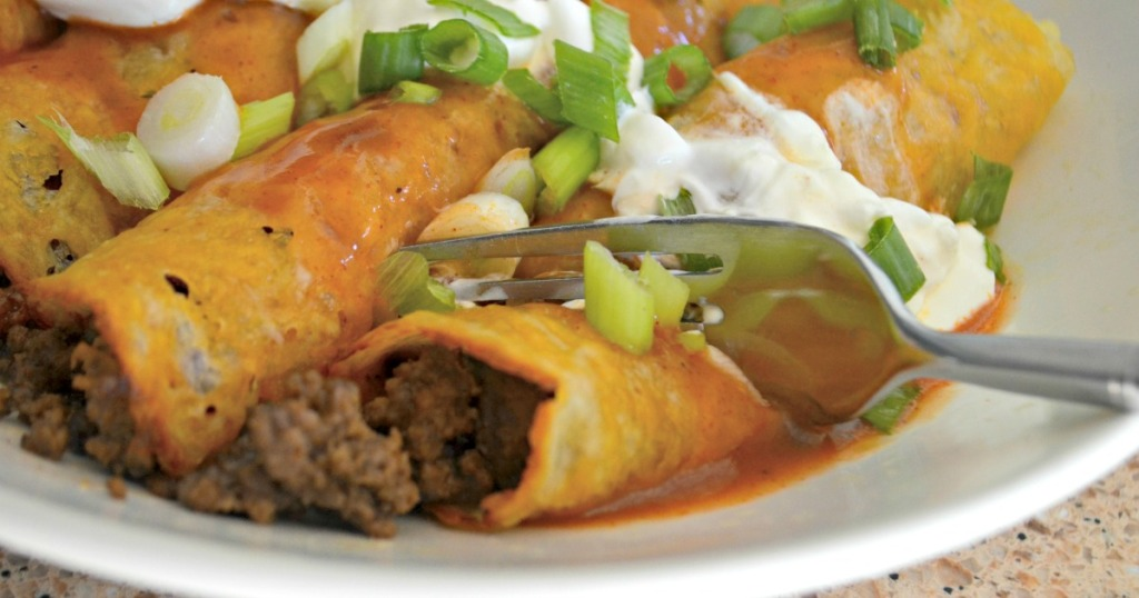 cutting into ground beef enchiladas