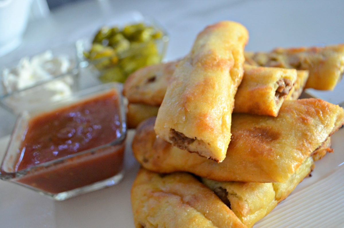 Easy Keto Taco Breadsticks - stacked on a plate with dipping sauces