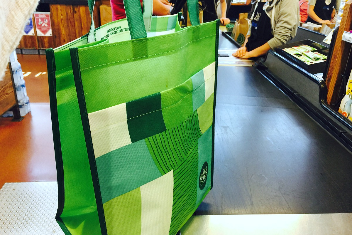 whole foods shopping tips — reusable grocery shopping bag in checkout line at whole foods