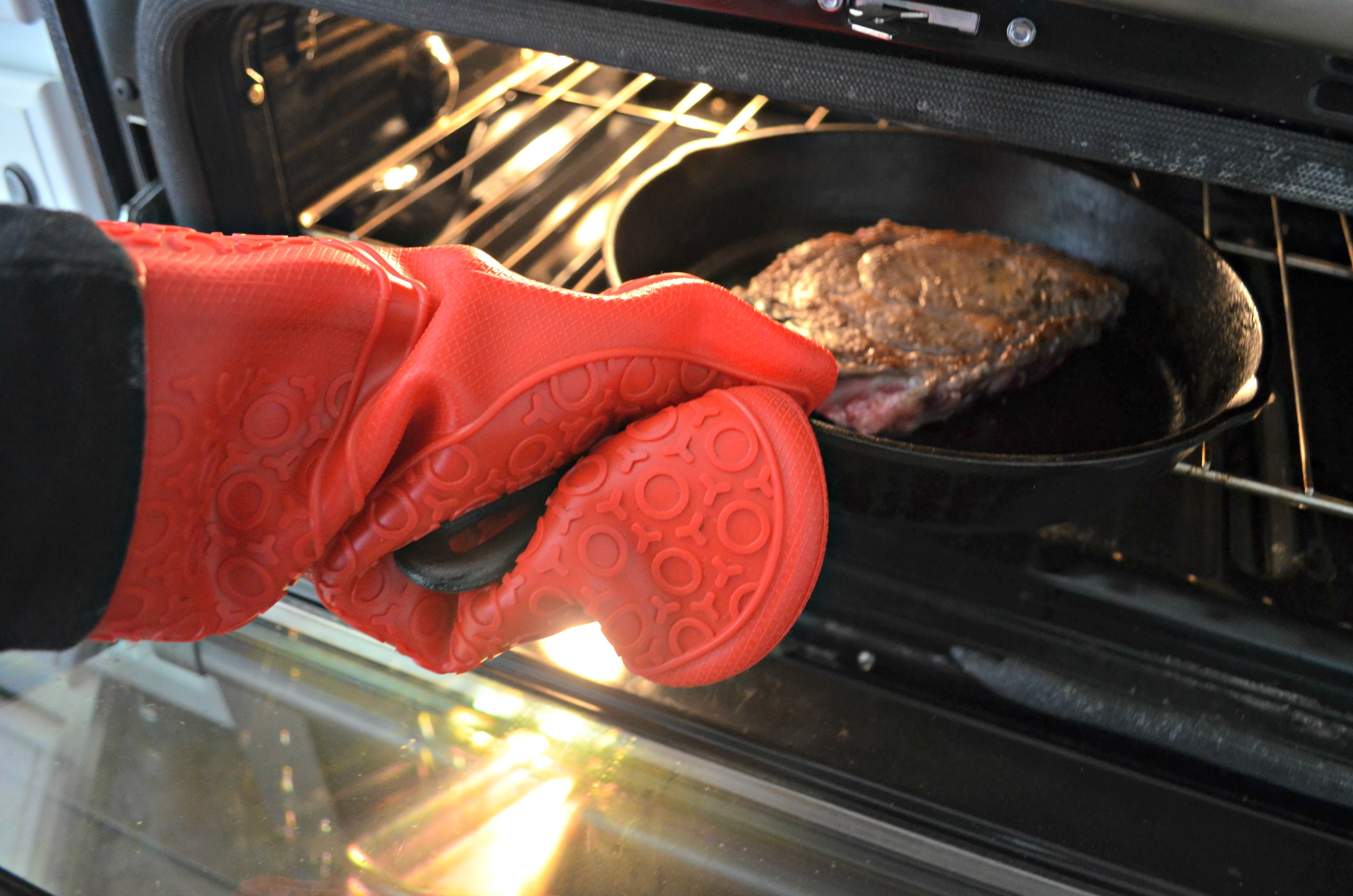 season, sear, and bake is the best way to cook steak – pictured here, pulling the pan from the oven