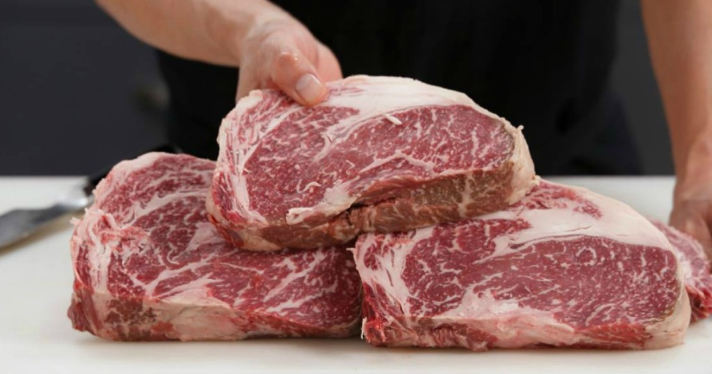 person holding uncooked steaks