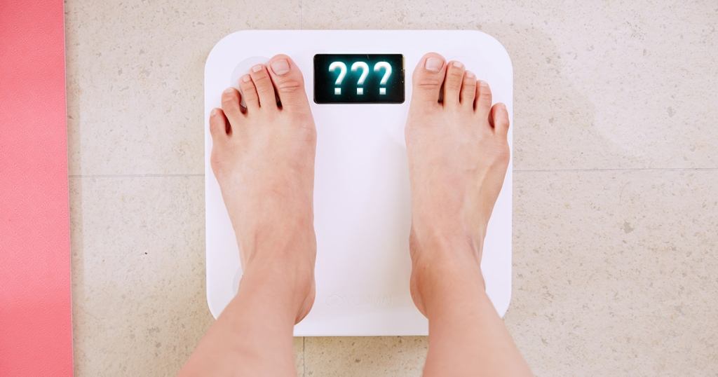 person on scale with question marks appearing for weight