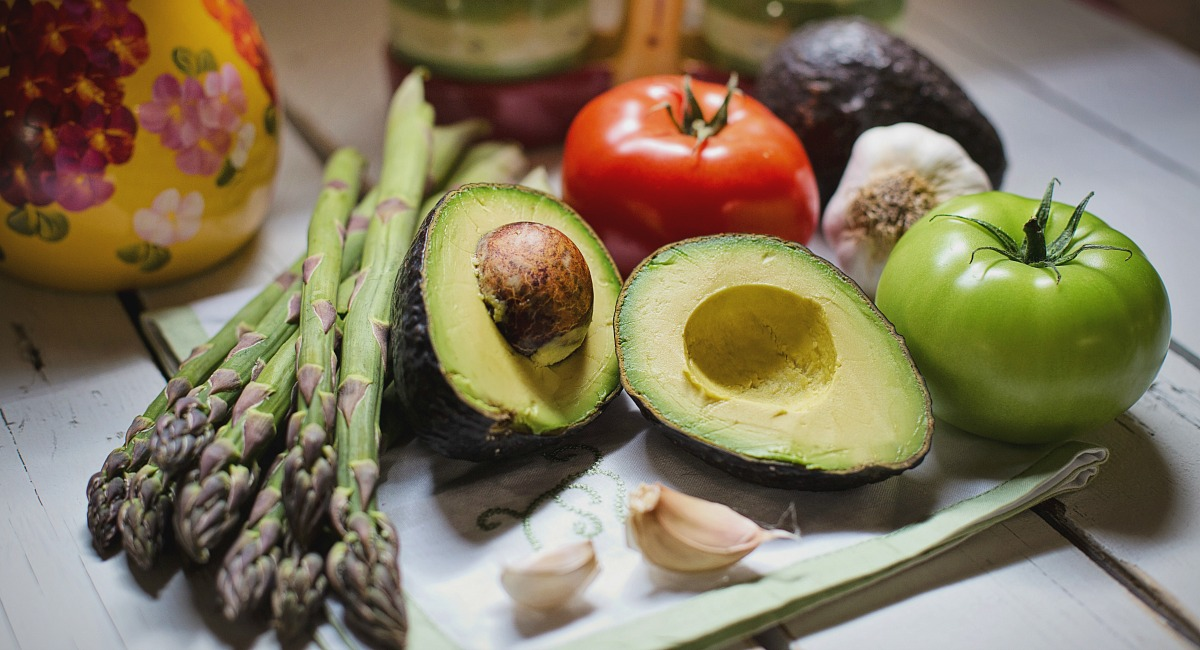 keto vegan diet — assortment of vegetables like asparagus, tomatoes, and avocados