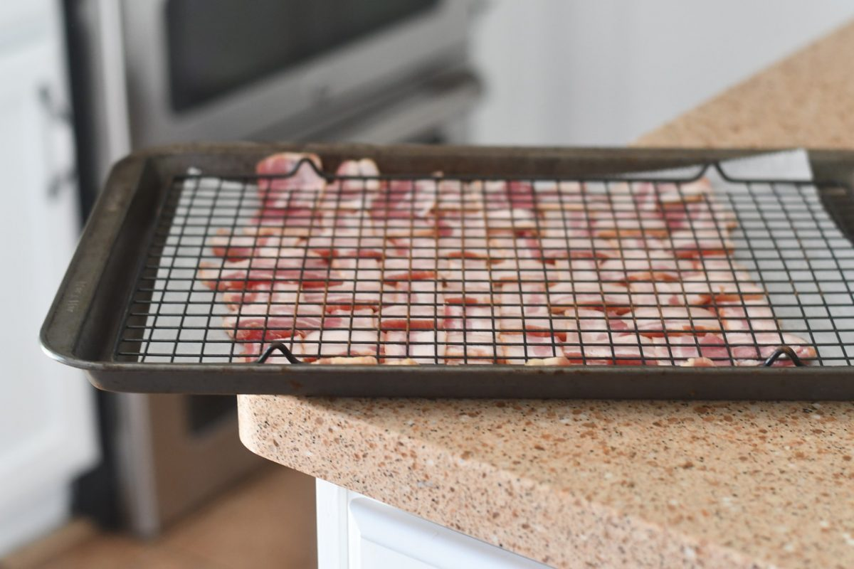 Keto BBQ Chicken Bacon Weave Pizza – pressing the uncooked bacon flat with a cooling rack