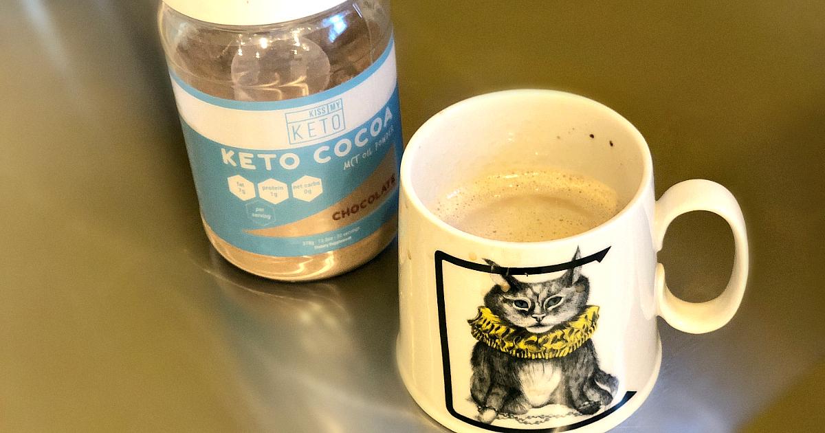 Kiss my Keto Cocoa Powder in a mug of coffee