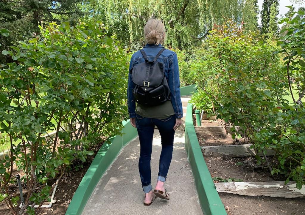 woman walking outside wearing backpack