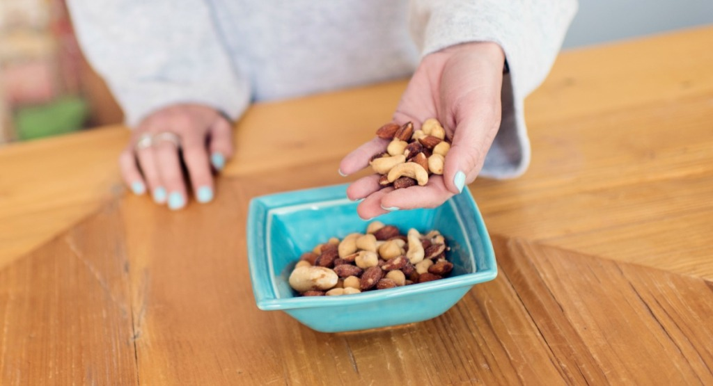 mixed nuts in hand for snacking before first meal