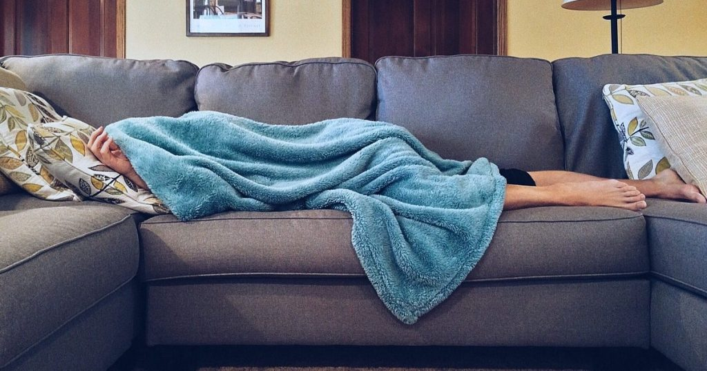 fatigued, tired person sleeping on couch