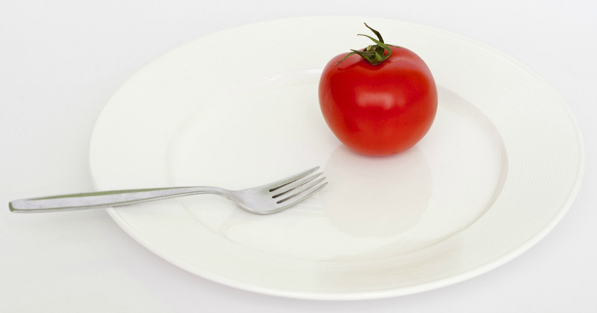 popular keto intermittent fasting plans eating schedules and tips — tomato on plate for restricted meals