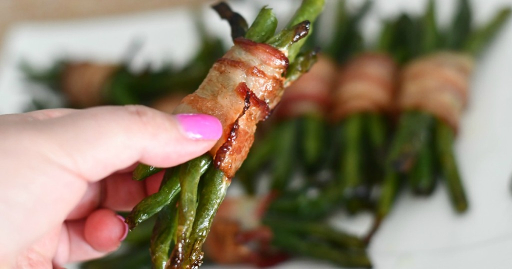 holding green been bacon wrapped bundle