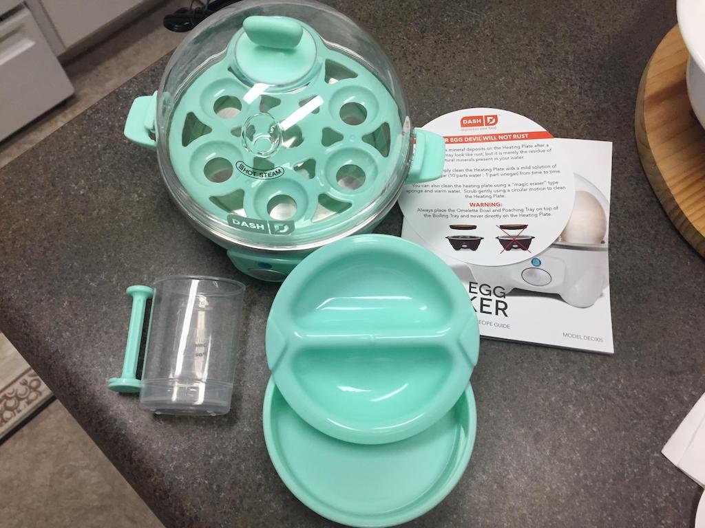 Dash mini egg cooker on counter with included tools and accessories