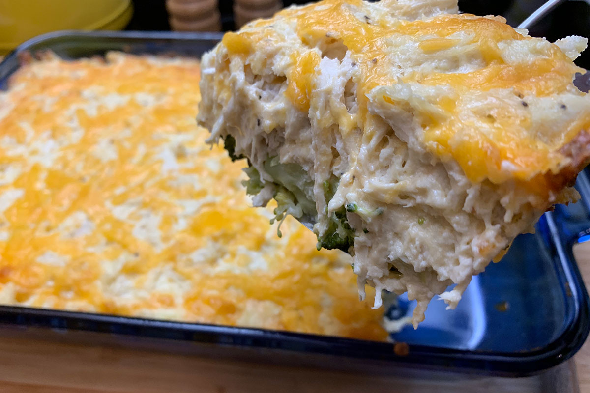 Low Carb Cheesy Chicken Casserole - a large serving of chicken casserole being scooped from a pan