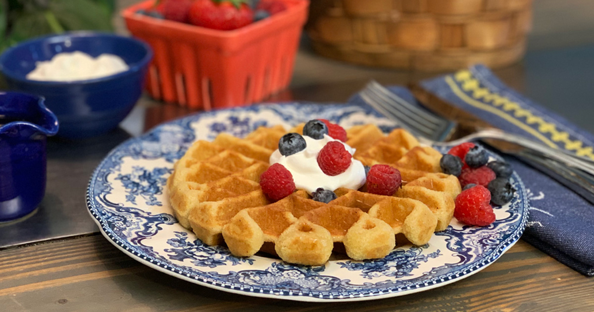 best delicious low-carb keto waffle recipe – on a plate with whipped cream and berries