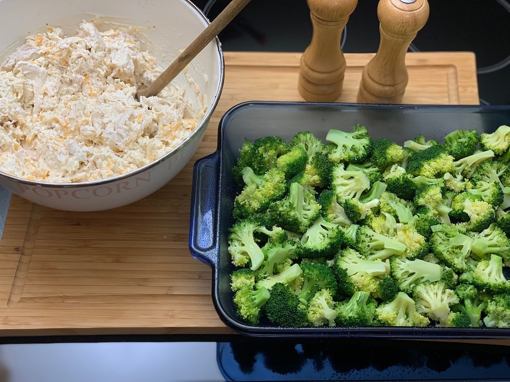bowl of shredded chicken mixture and broccoli with casserole dish