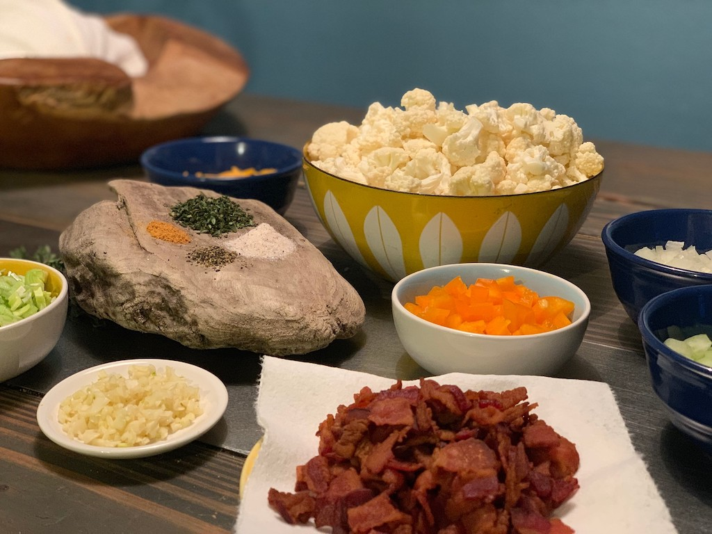 cauliflower in bowl, bacon on paper towel, and other keto ingredients in bowls