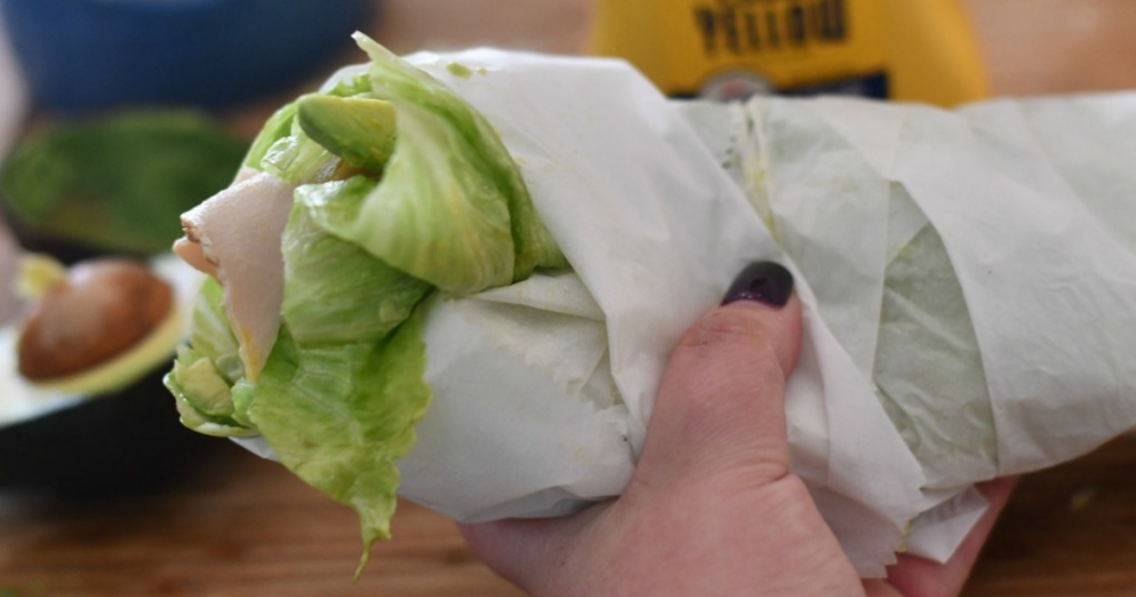 holding homemade lettuce wrapped sandwich