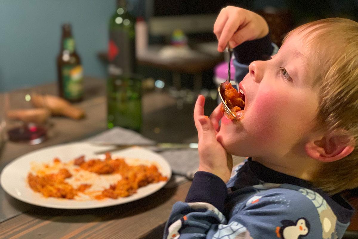 Keto Italian Sausage and Spaghetti Squash Casserole - young boy eating a large bit of Italian squash casserole