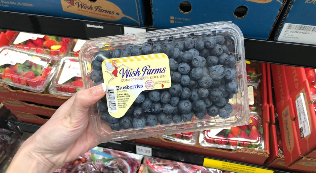 holding pack of blueberries fruits in produce section