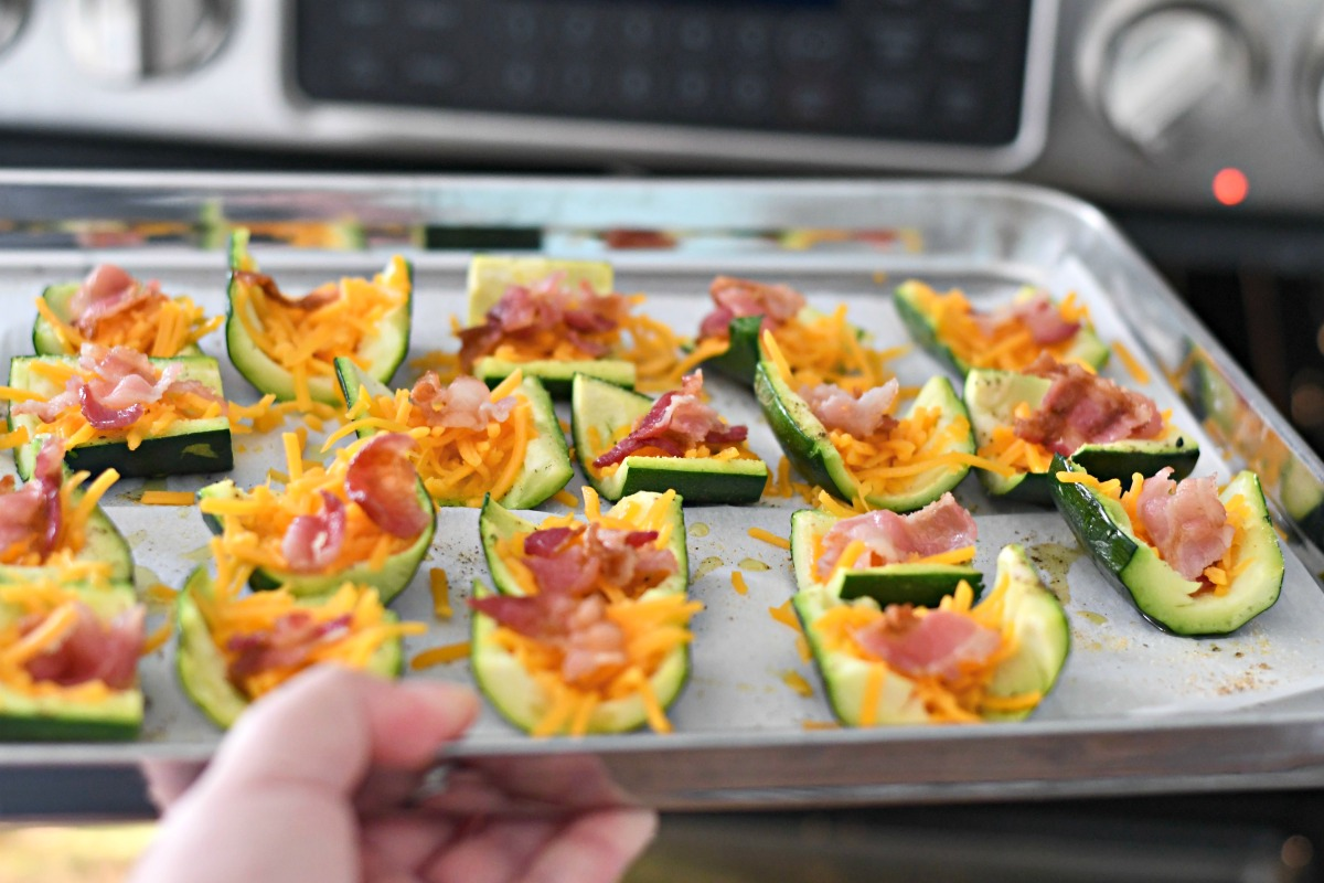 keto loaded zucchini skins recipe ready for a second baking, topped with cheese and bacon