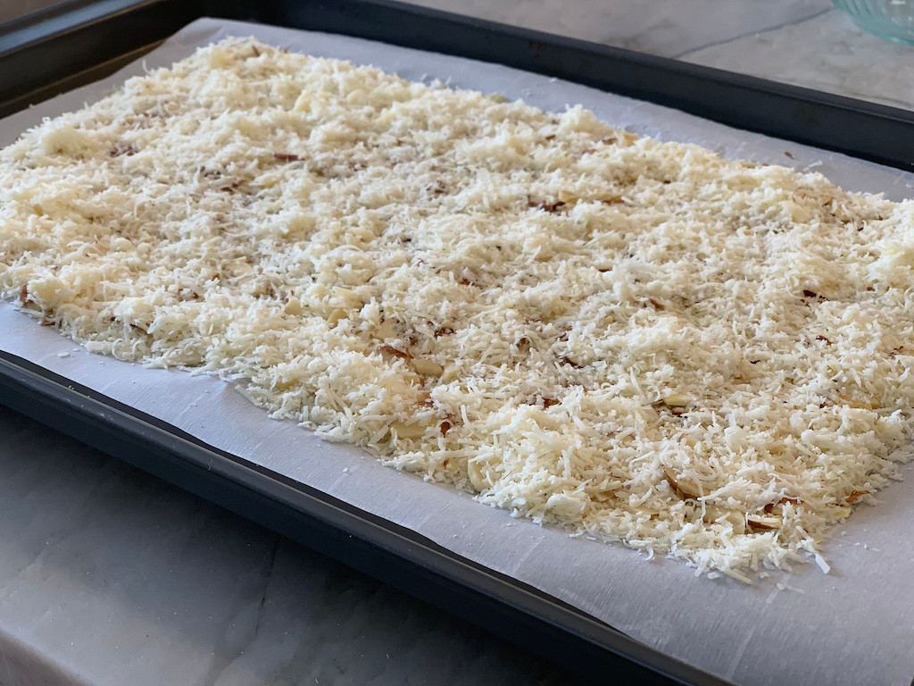 shredded parmesan cheese and almonds on sheet pan with parchment paper
