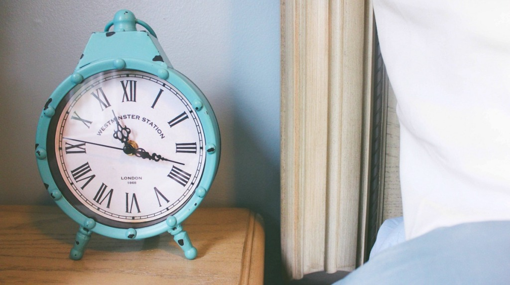 alarm clock on nightstand next to bed